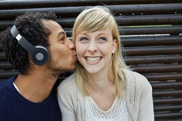 Young man with headphones kissing woman