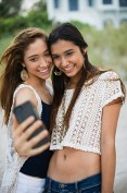 Teenage girls (16-17) taking picture of themselves using phone