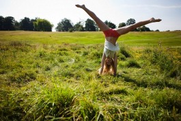 Young woman doing a handstand in a field