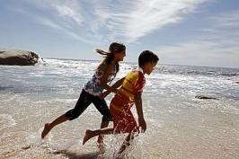 Children (10-12) running on beach