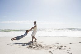 Father swinging son around on a beach