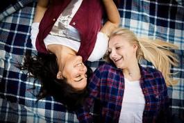 Teenage friends (16-17) lying down on blanket