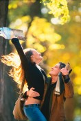 Excited couple embracing each other outdoors in Autumn