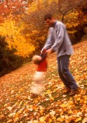 Father with his son playing outdoors in autumn