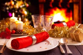 A romantic Christmas dinner table setting with candles and Christmas decorations. A fire is burning in the fireplace and Christm