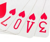 Suit of hearts playing cards spelling the word love on white