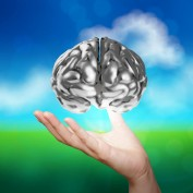 businessman hand showing 3d metal human brain on nature background as concept