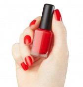 Woman hand manicure with red nail polish bottle
