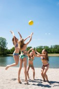 Four girls in bikinis playing with ball at bathing lake