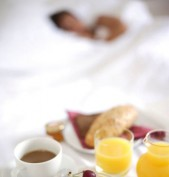 Woman asleep in hotel bed (breakfast tray in foreground)