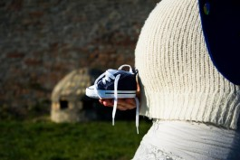 Pregnant woman sitting on a bench with baby shoes in front of a belly