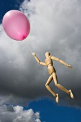 Wooden manikin flies away holding a pink balloon