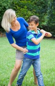 Mother and son playing baseball in yard