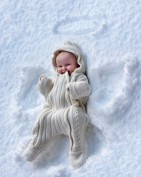 A baby girl makes a snow angel pattern in the snow.