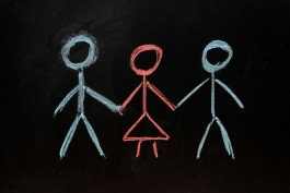 2 men and 1 woman drawn on a blackboard in chalk.