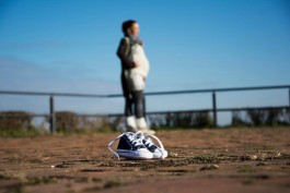 Baby shoes close up with pregnant woman behind in a distance in blur
