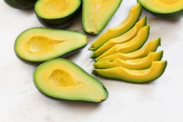 Avocado pieces and halves with bright yellow fruit pulp on white stone board
