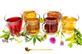Various colorful herbal tea collection in glass cups on white background